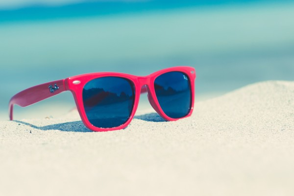 guide to make a packing Red sunglasses on a sunny beach